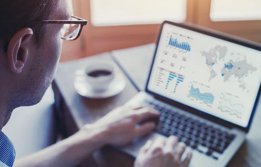 A business analysts looks over statistics on his laptop and looks for trends on graphs.