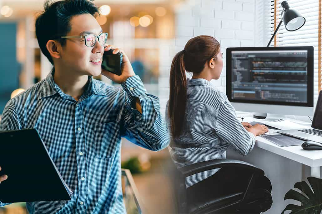 a man with laptop in hand and talking on phone with a girl in background coding something on desktop
